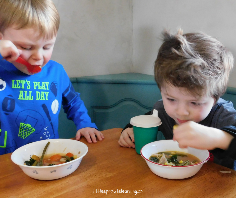 two boys sitting at a table eating stone soup or friendship soup