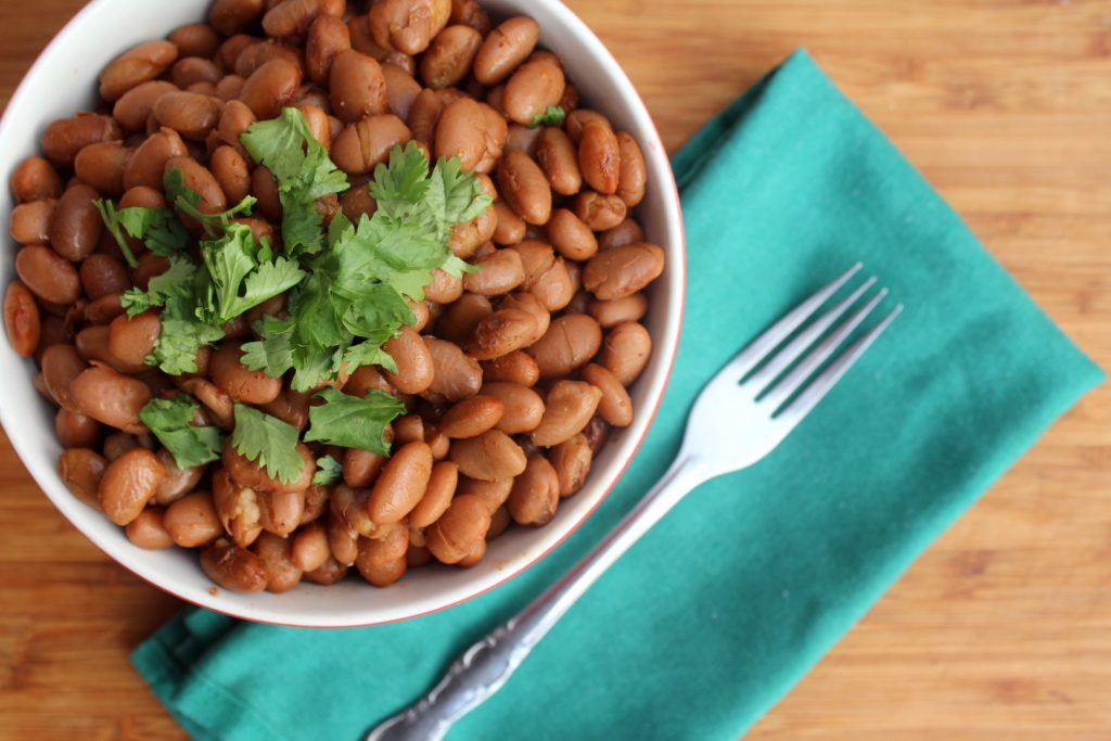 bowl of beans on cutting board with napkin and fork, garnished with cilantro