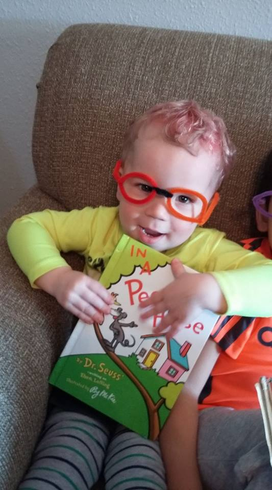 Dr. Seuss Activities for Preschool, preschooler wearing pipe cleaner glasses holding Dr. Seuss book for developmentall appropriate practice