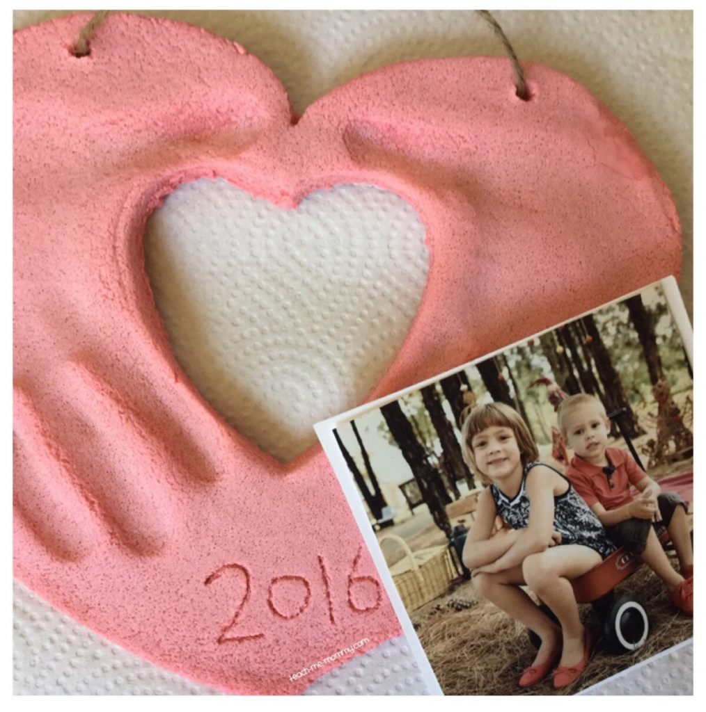 pink salt dough picture frame with heart cutout for photo, handprints pressed in dough.
