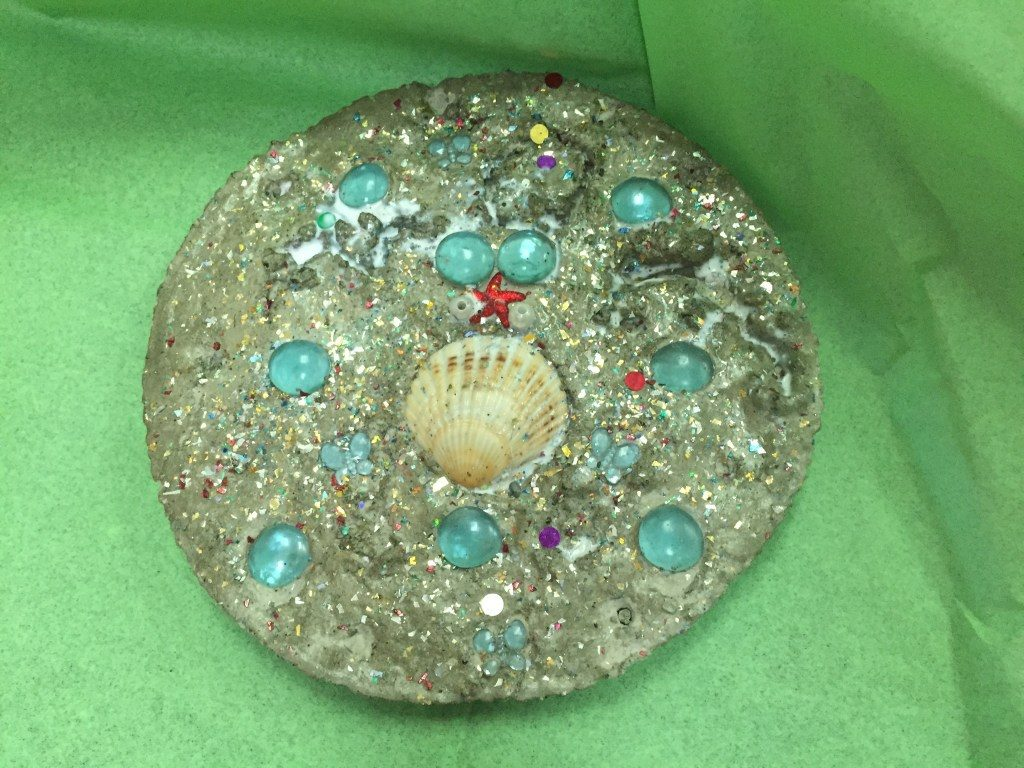 Cute garden art stepping stone with marbles, shells and beads.