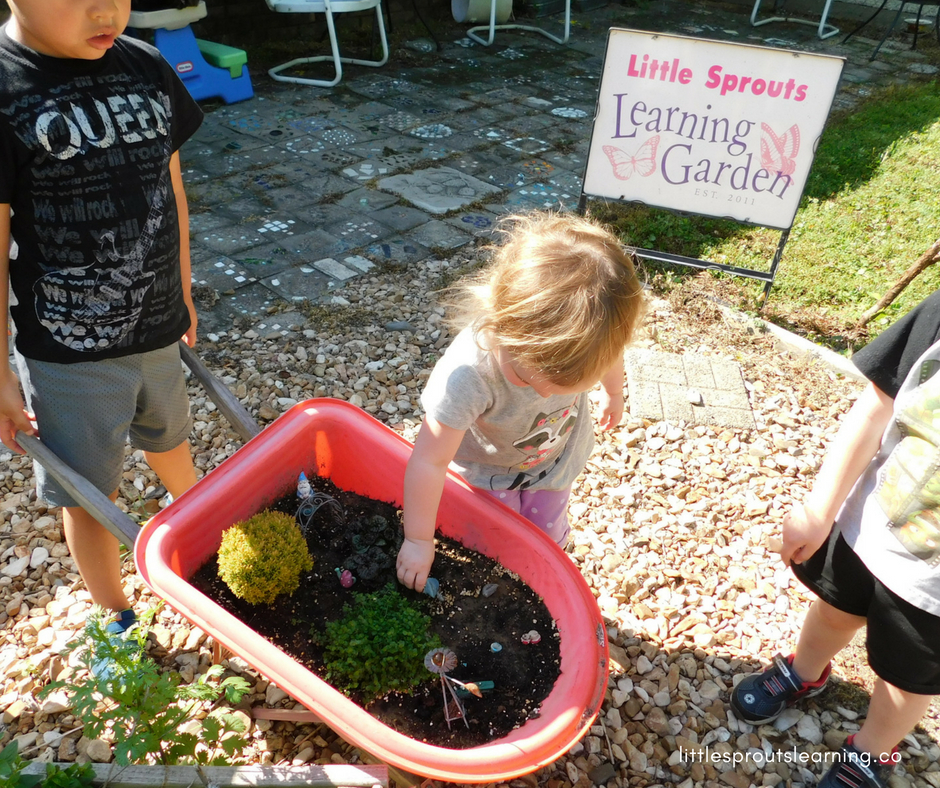 Kids playing with a fairy garden