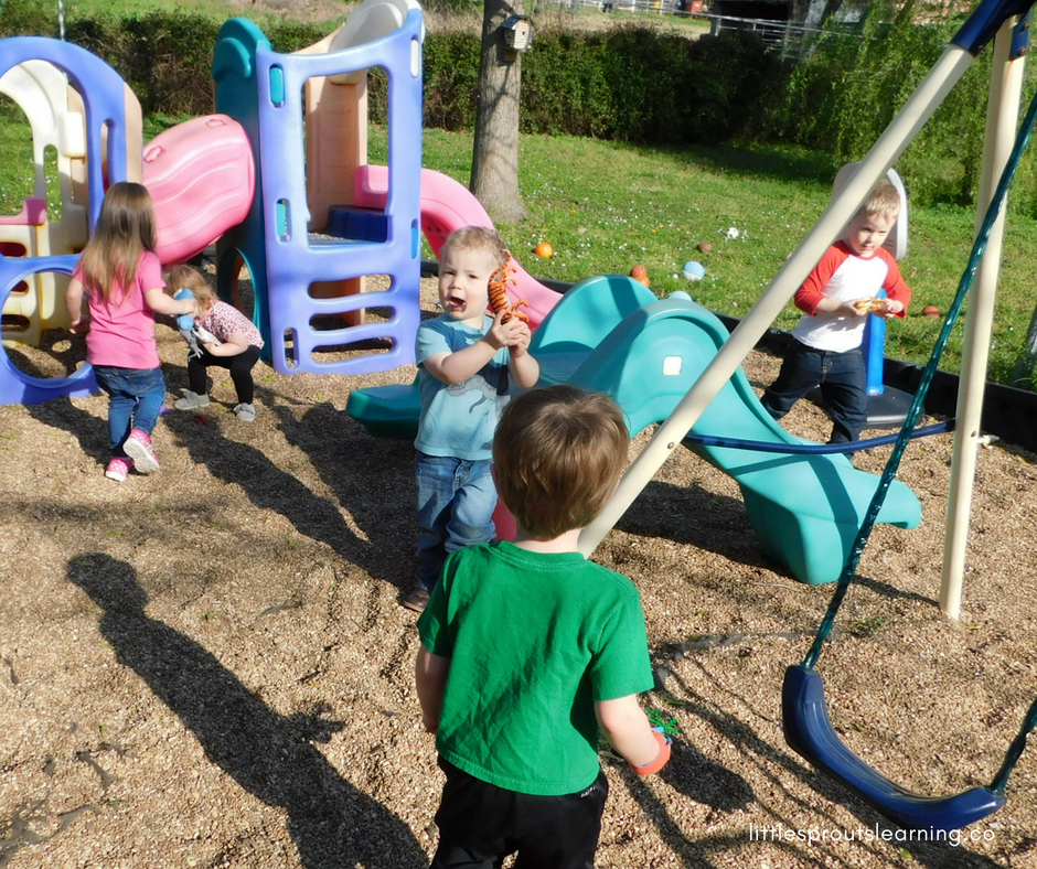 kids hunting for plastic animals on preschool playground.