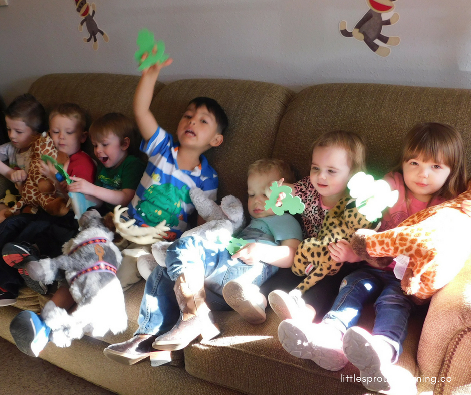 kids sitting on the couch playing with stuffed animals and frog finger puppets.