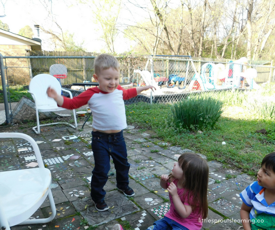 preschool kids playing animal cherades. One child is acting out an animal while the others are watching