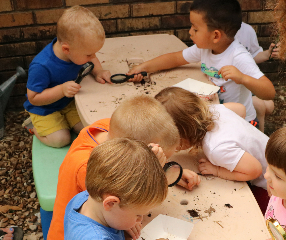 Kids observing worms and compost under magnifying glass