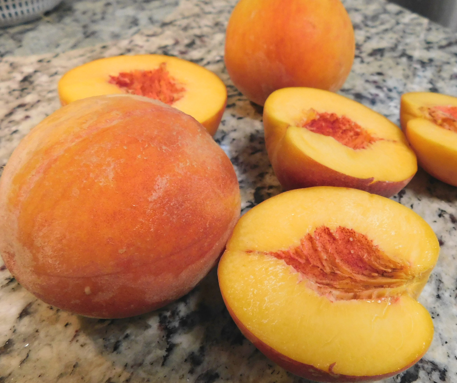 peaches on the counter, some whole and some cut in half