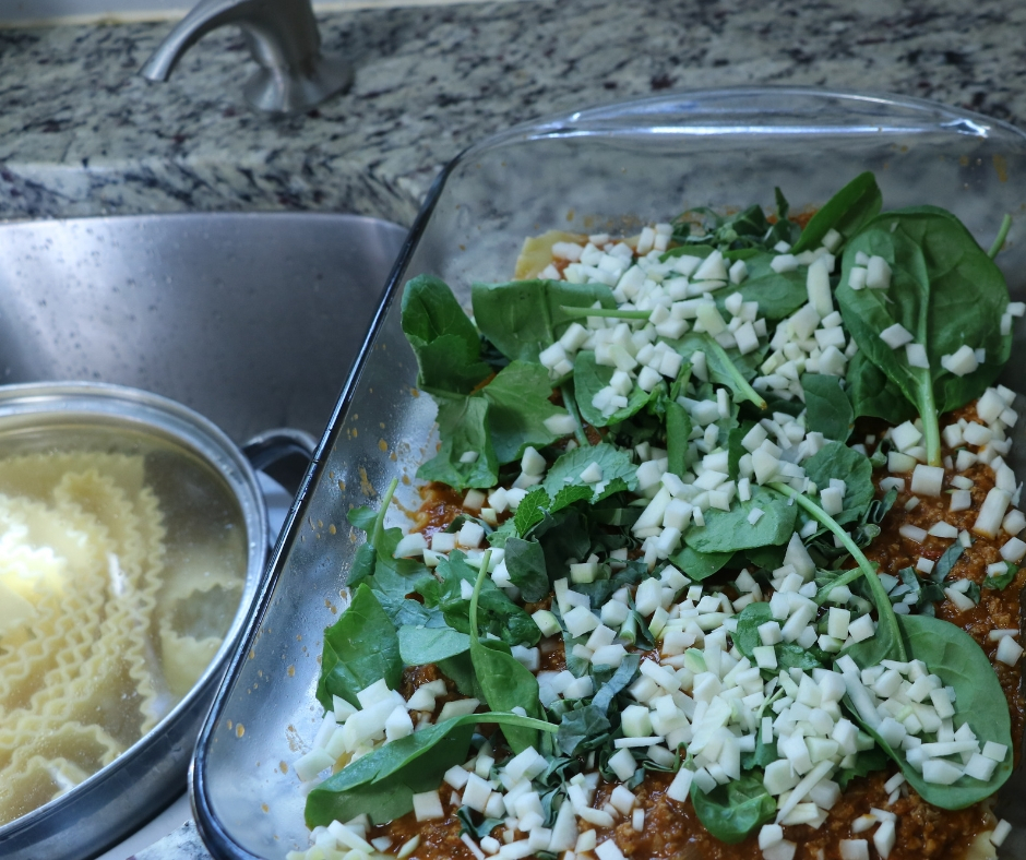 lasagna pan layered with ingredients as it's being built