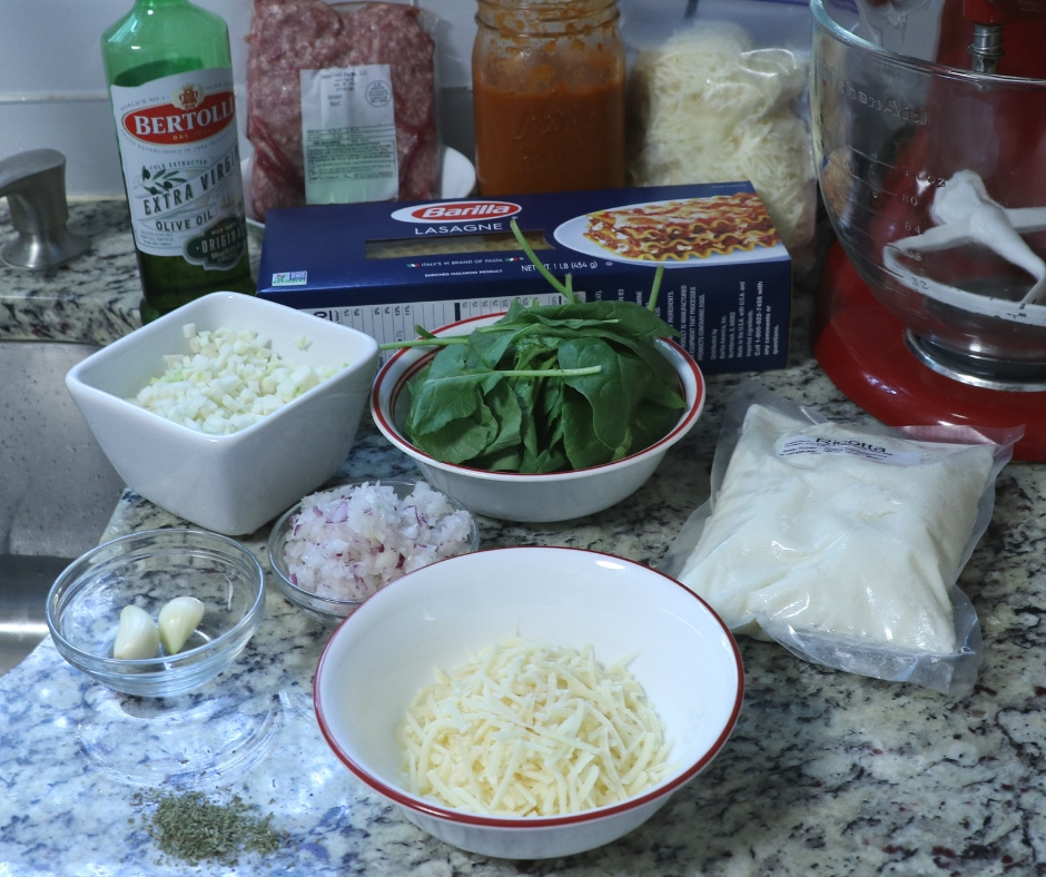 ingredients for vegetable meat lasagna, onions, garlic, riccota cheese, parmesan cheese, mozzarella cheese, spinach, lasanga noodles, ground beef, olive oil, kohlrabi and oven roasted tomato sauce