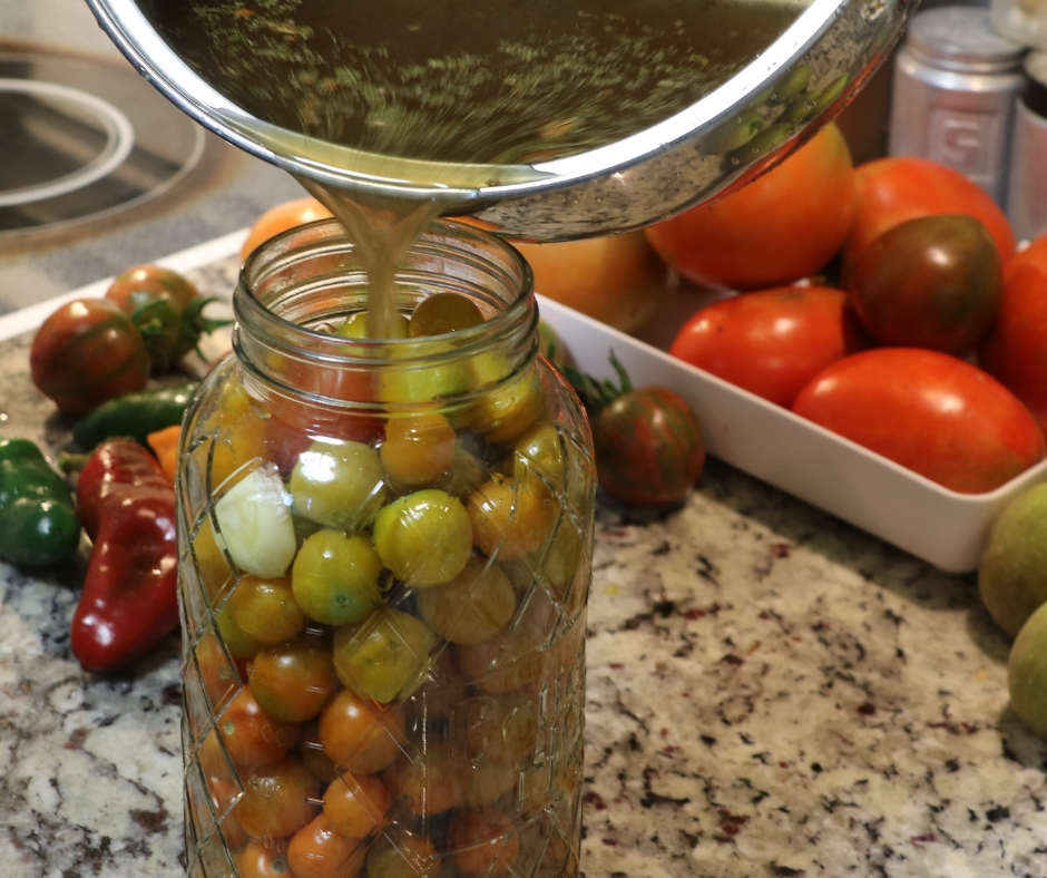 Easy Refrigerator Pickled Cherry Tomatoes. Pickling liquid being poured into jar full of cherry tomatoes to make refrigerated pickled cherry tomatoes