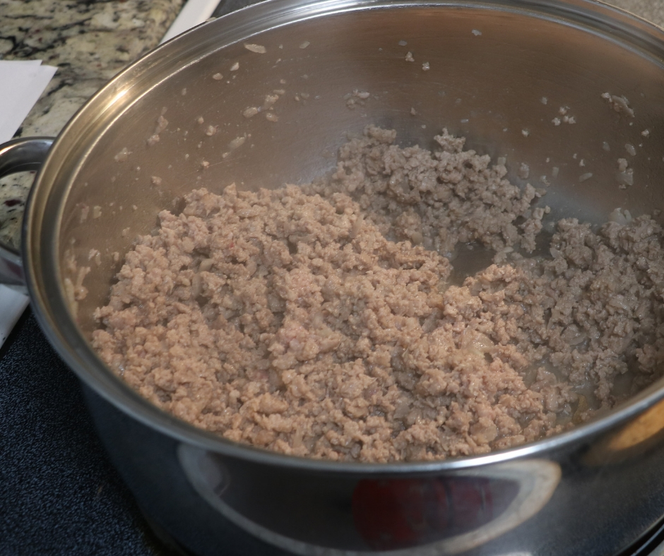 browned ground beef in a pan on the stove