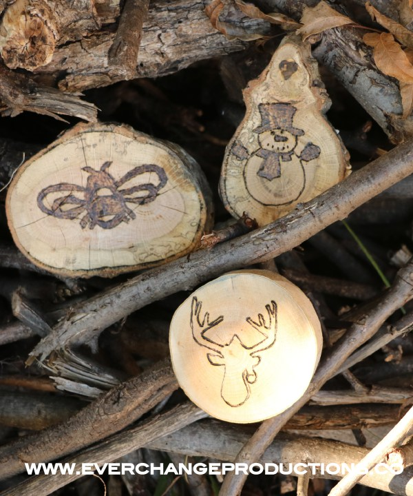 Three wood burned wood slice ornaments arranged in a wood pile