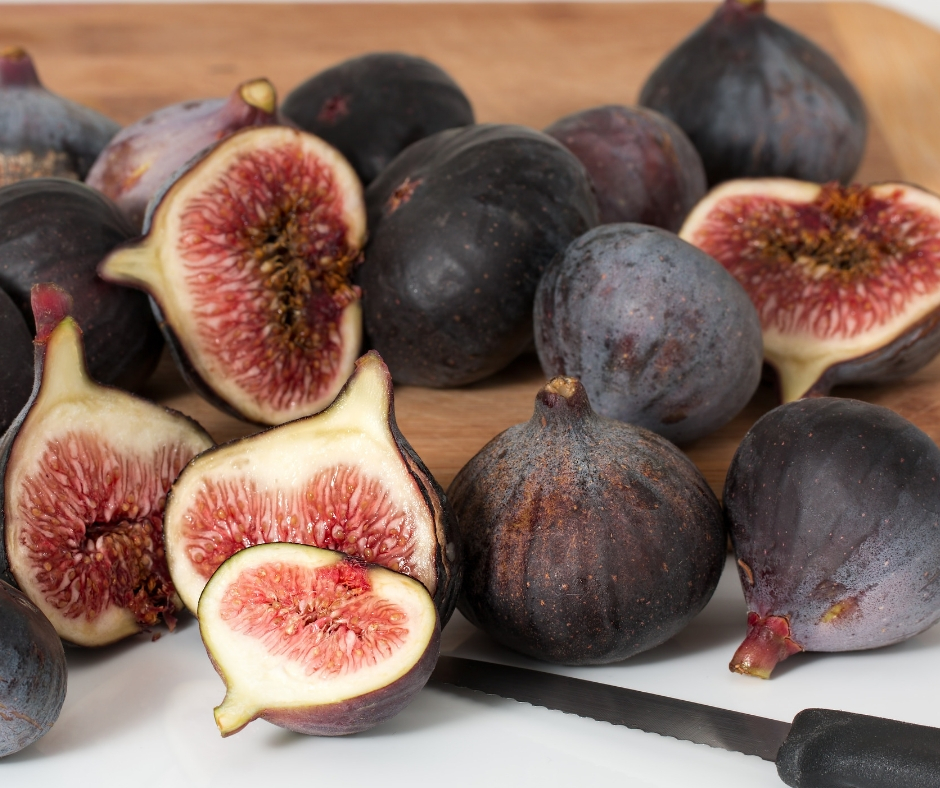 Cutting board full of brown figs cut in half