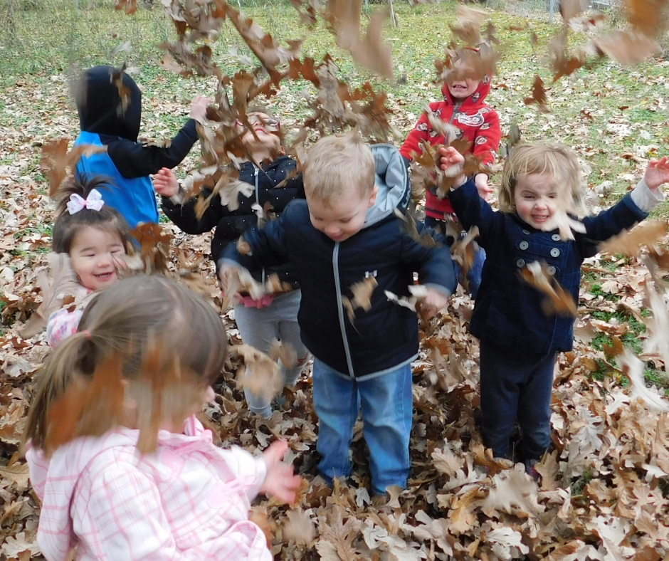 kids having fun at daycare throwing up leaves and playing in them.