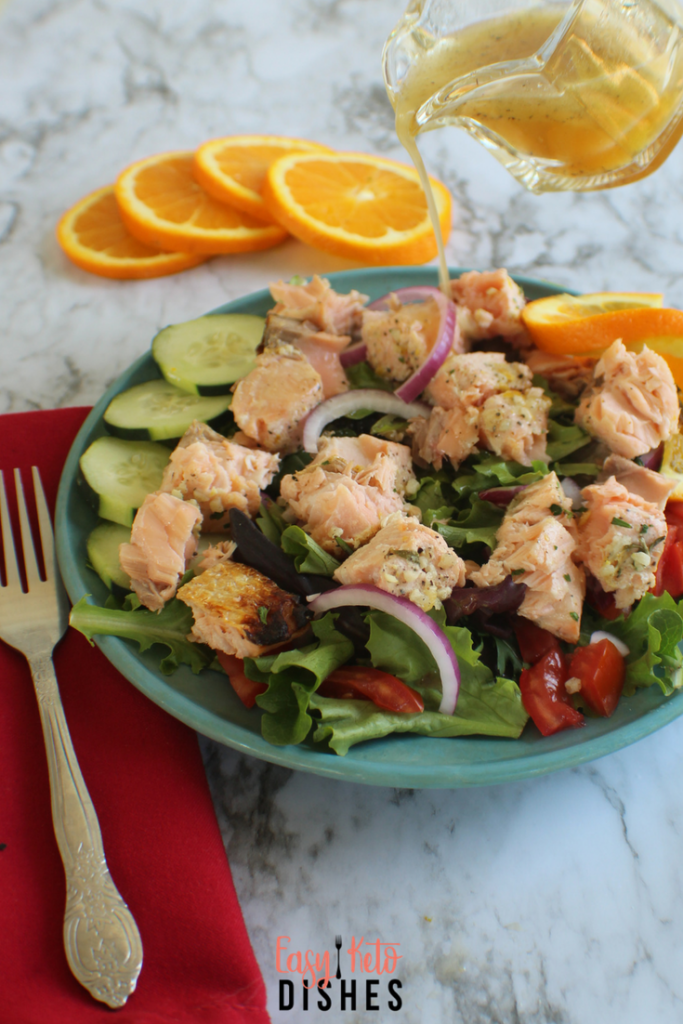 salmon salad on a plat on a counter with a fork, napkin and oranges
