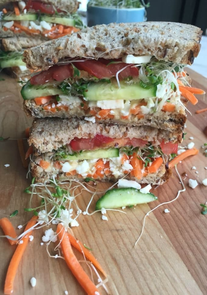 veggie sandwich with sprouts on cutting board.