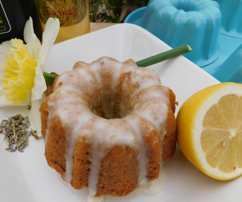 tiny honey lavender bundt cake with lemon honey glaze on plat with daffodil, lemon and dried lavender.