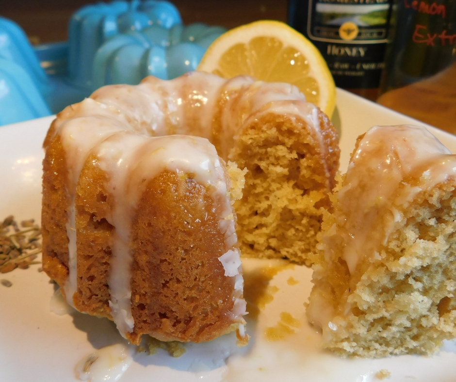 honey lavender bundt cake with glaze, a piece cut out on a plate wtih lemon behind