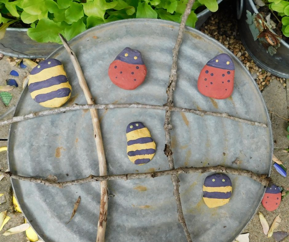 tic tac toe board on the bottom of a bucket with wooden sticks and painted rocks garden games for kids