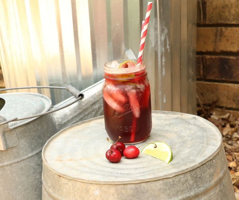 Cherry limemade in mason jar with paper straws and a lime wedge and three cherries on bucket in the garden
