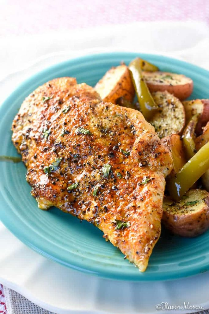Sheet pan one pot wonder served on a plate with chicken breast and veggies to the side