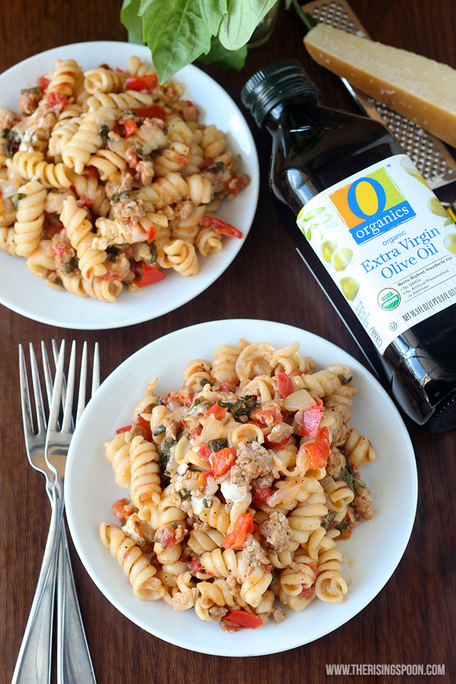 One pot wonder pasta with sausage in bowl on the table with forks and olive oil on side.
