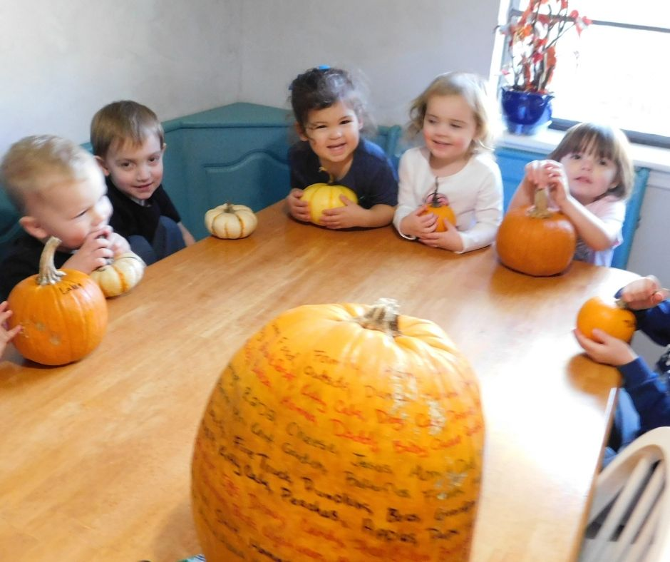 kids sitting around table with pumpkins and big pumpkin with things they are thankful for written on it.