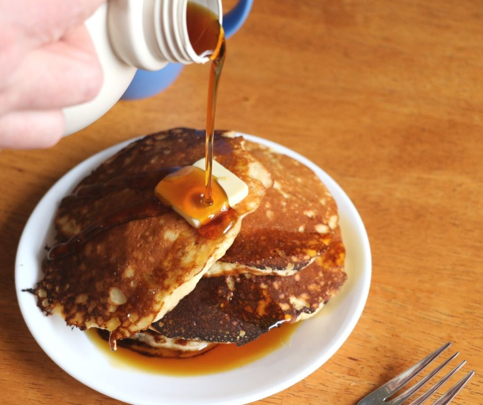 healthy pancakes for kids, on a plate with butter and pouring syrup on