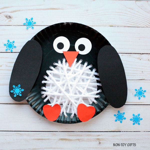 penguin made from a paper plate, construction paper and yarn on a table