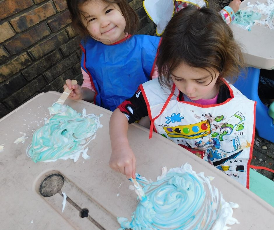 kids using shaving cream paint on a picnic table outside wearing smocks