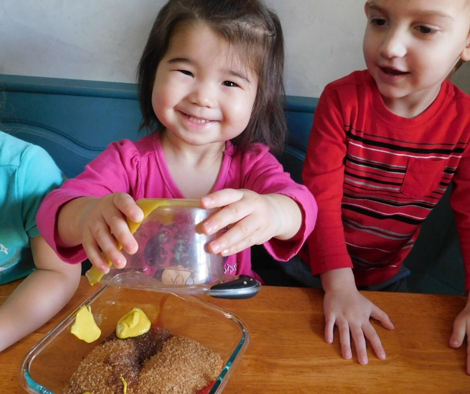 child adding food to bowl in kids cooking classes for preschoolers