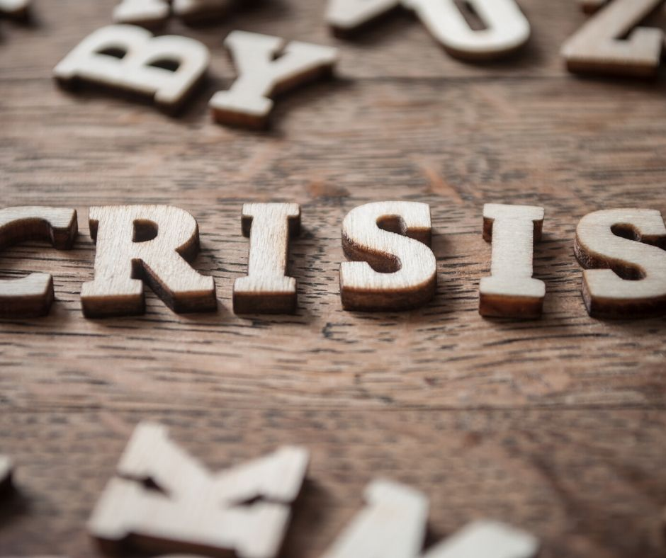 letters strewn around on a table with crisis spelled out