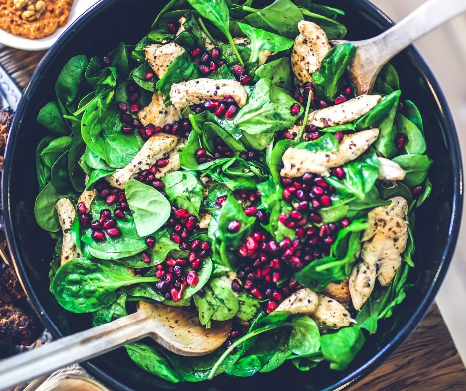 Salad with chicken, spinach, and pomegranites