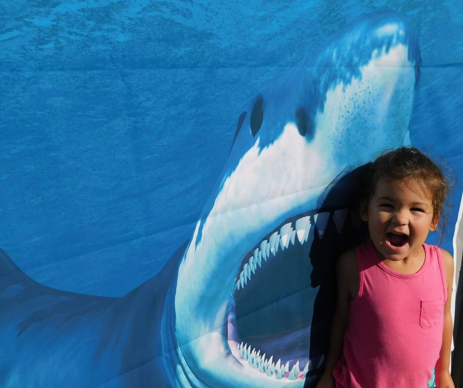 child pretending to be eaten by shark picture for photo op at shark party