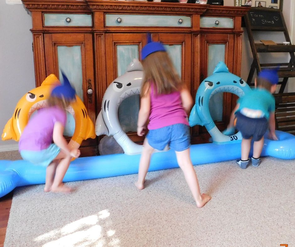 kids playing shark ring toss at shark party
