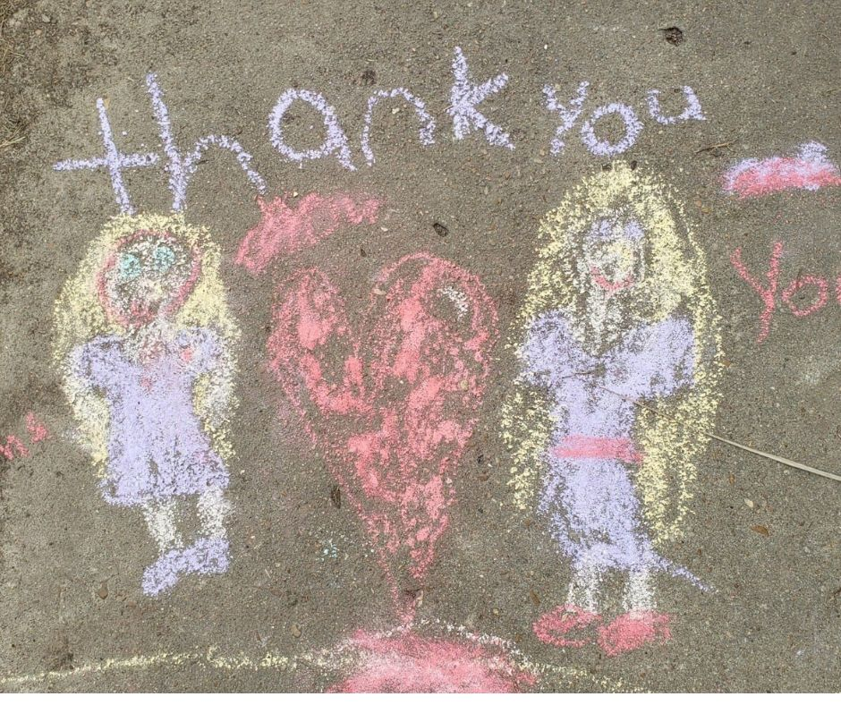 Chalk drawing that says thank you and has a heart and two people. It says you, me.