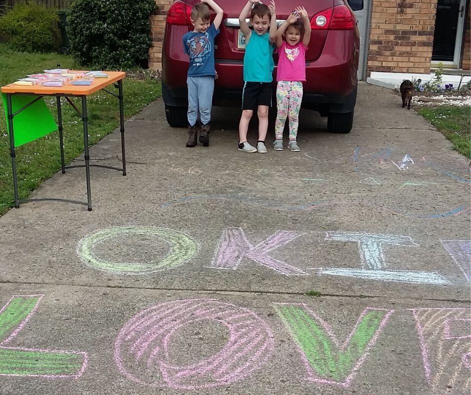 kids by a car showing their sidewalk chalk on the driveway for chalk my walk