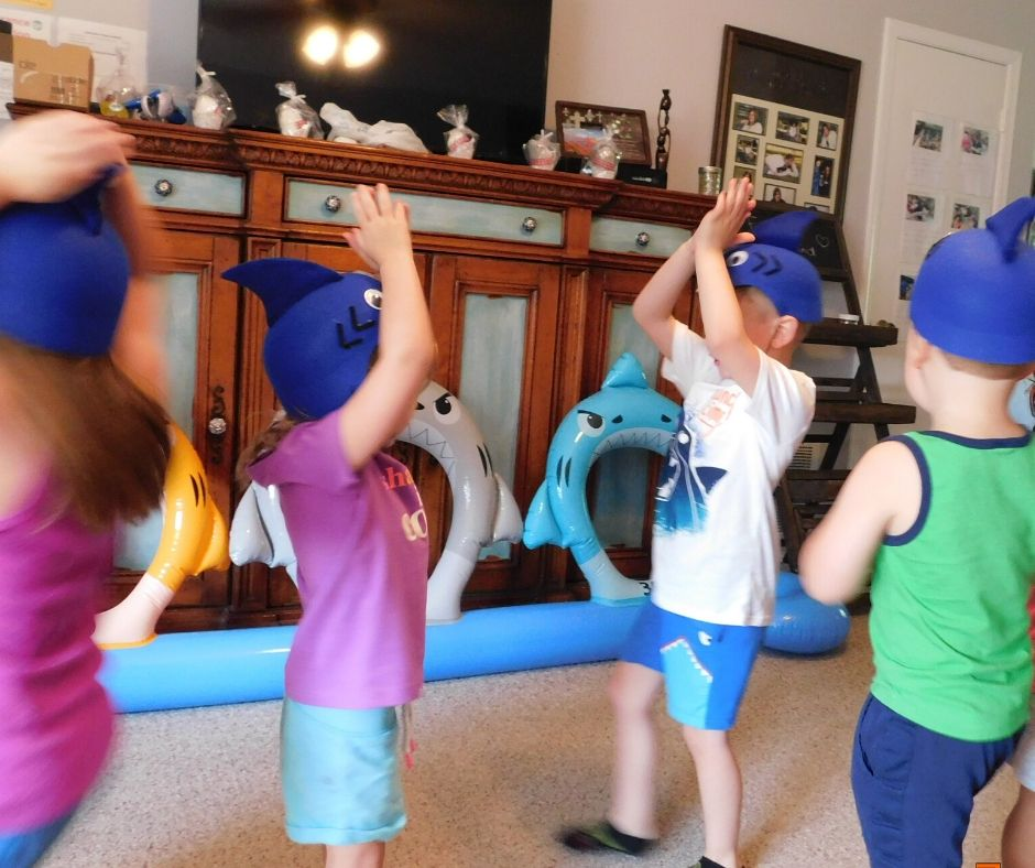 kids playing with shark hats, singing and making shark fins on top their heads