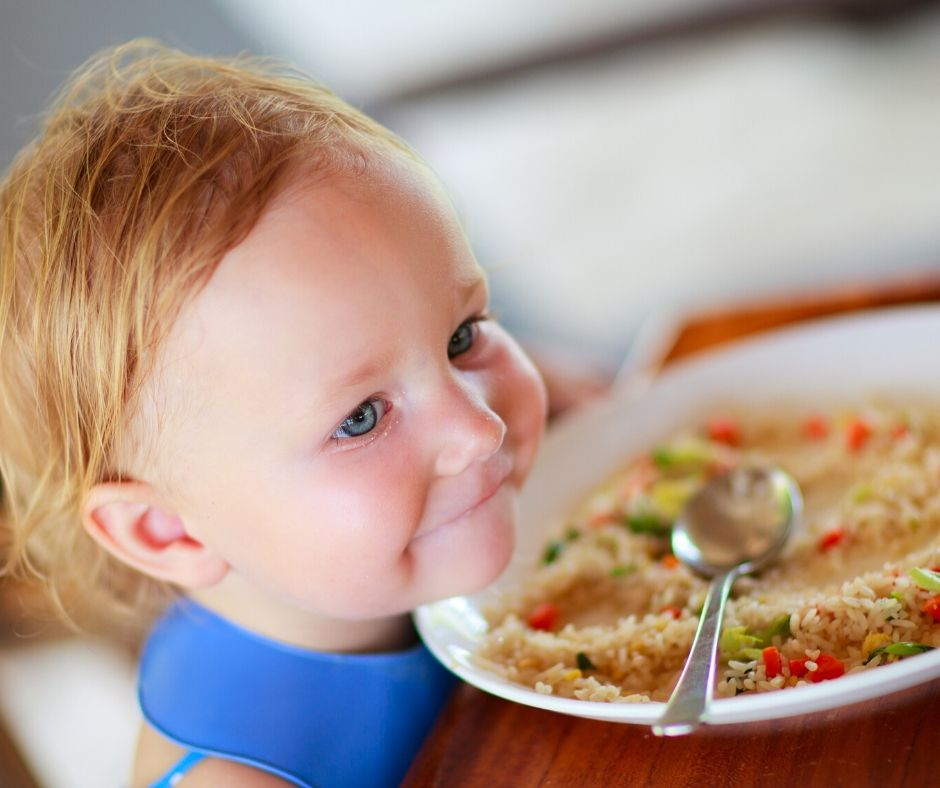 child at the table with plate of rice and vegetables