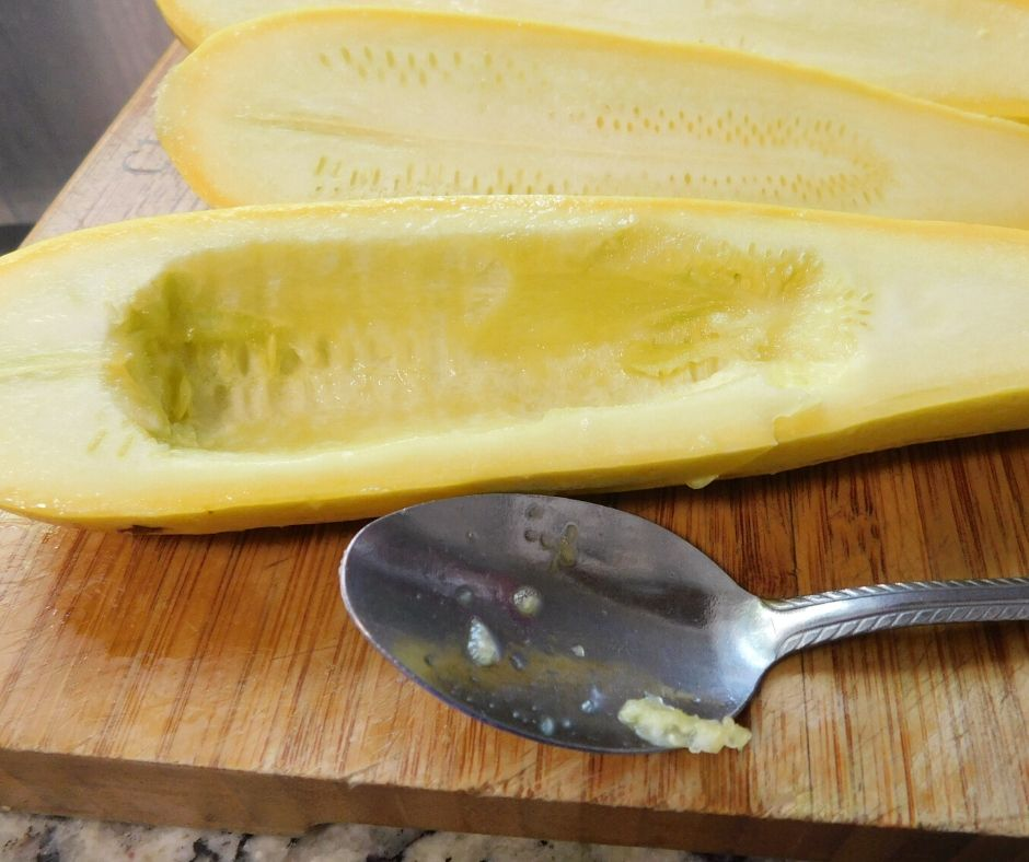 yellow squash with center scooped out with a spoon on a cutting board