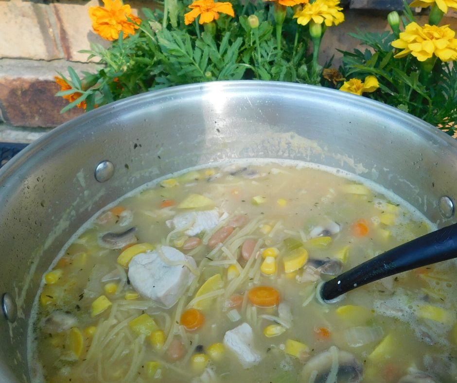 big pot of summer squash soup on the table with marigolds and brick behind