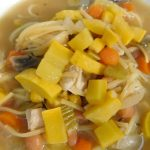 summery squash soup with carrots, noodles, chicken, mushrooms, celery and more on the table with a spoon.