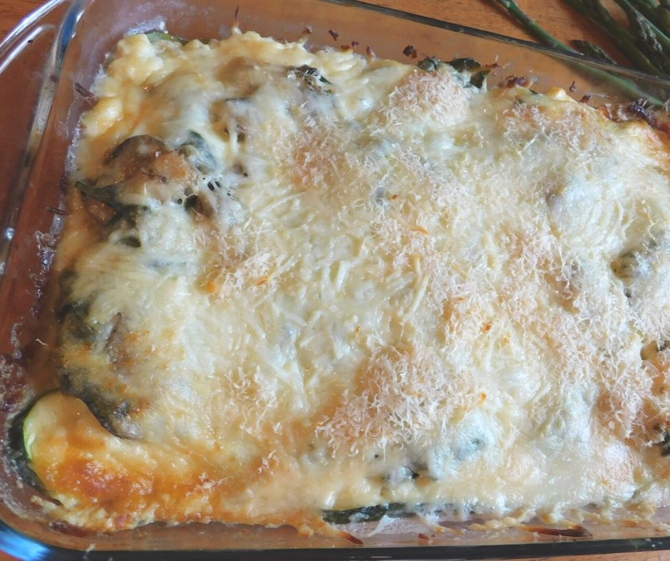 Nightshade free vegetable lasagna in a pan showing melty cheese and a few green veggies peeking through