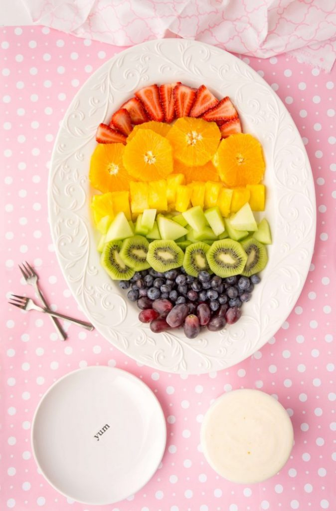 rainbow fruit plate with colorful strawberries, oranges, pineapple, honeydew, kiwi, blueberries, and grapes