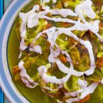 pork verde in a bowl toped with sour cream