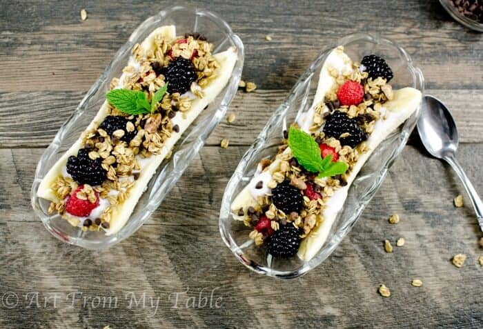 banana splits made with fruit and yogurt in boats, topped with a sprig of mint