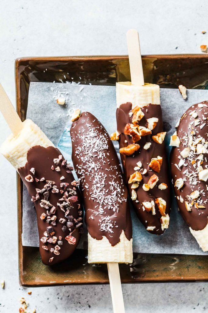 chocolate dipped bananas with toppings on popsicle sticks