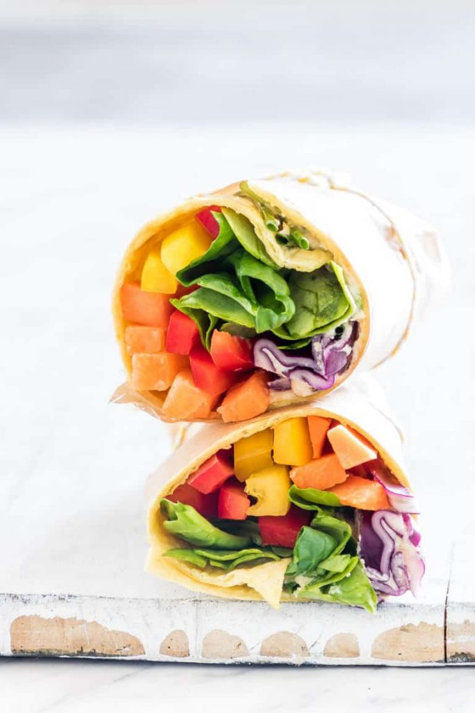 rainbow colored vegetable wraps stacked on a cutting board