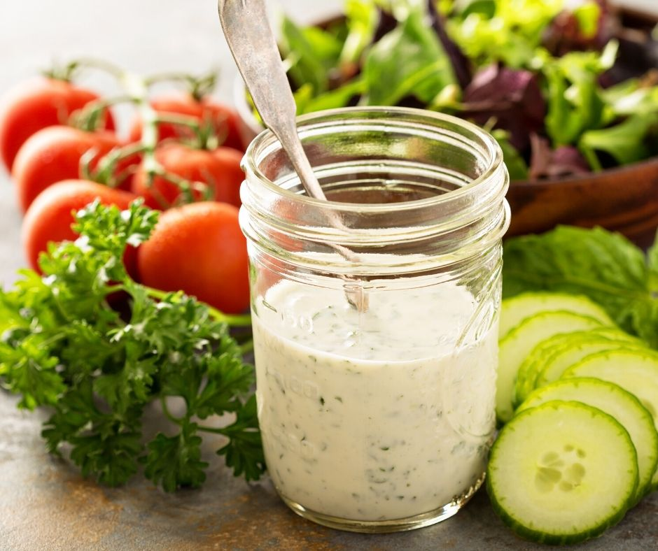 jar of homemade ranch dressing surrounded by crisp fresh veggies