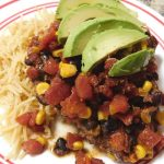 slow cooker pork chops with rotel, corn, and black beans topped with avocado slices and a side of pasta